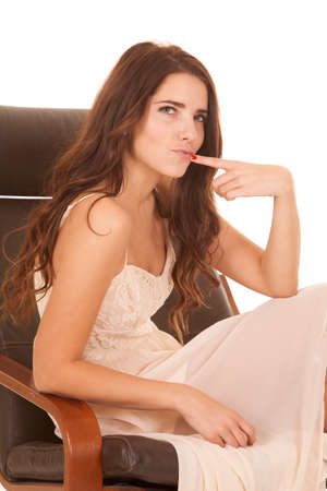 A woman is sitting in a chair with her finger to her lips thinking. photo