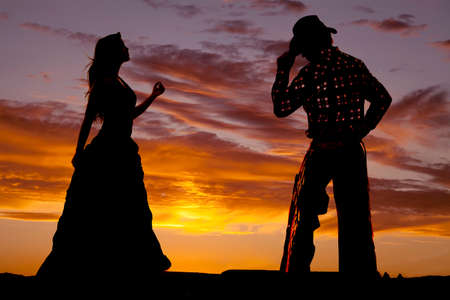 A silhouette of a western cowboy and lady.