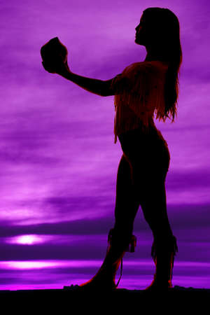 A silhouette of a Native American woman holding a pot. photo