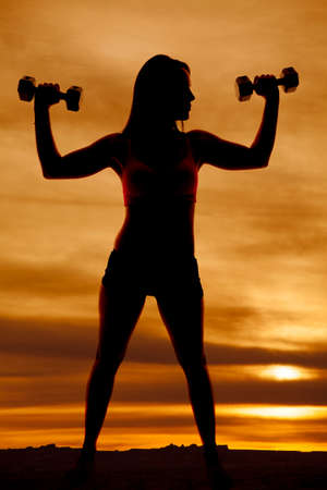 A silhouette of a woman holding up weights. photo