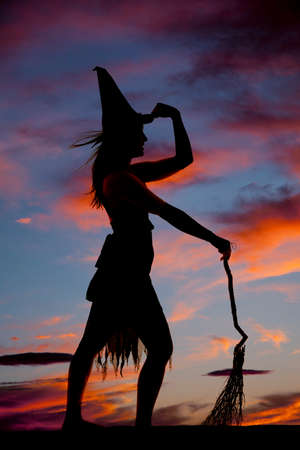 A silhouette of a witch holding her hat and broom.