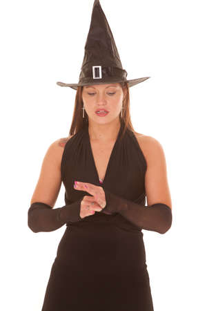 A witch is looking down at her hands.
