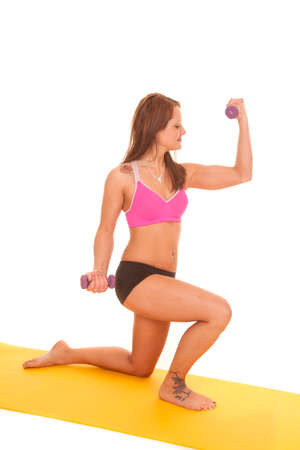 A woman is flexing while curling weights on a mat. photo