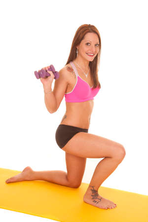 A woman is holding weights while kneeling on a mat. photo