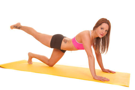 A woman is doing push up while holding up her leg. photo