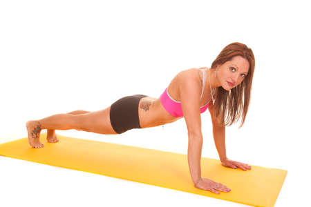 A woman is doing a push up on a yoga mat.