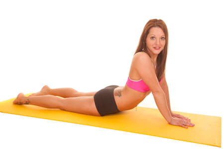 A woman is doing yoga on a yellow mat. photo