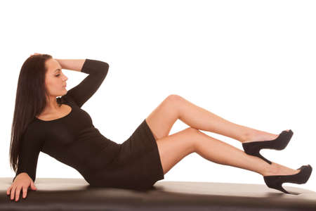 A woman in a black dress laying back with her legs out. photo