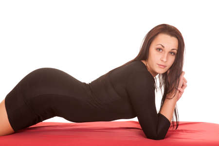 A woman in a black dress laying on her stomach looking. photo