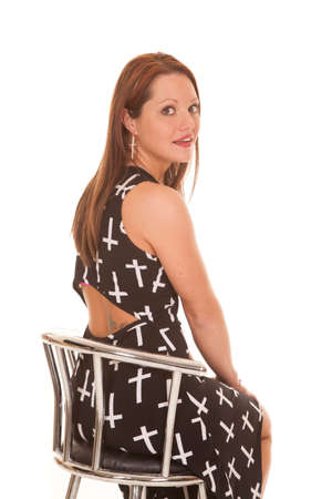 A woman is sitting in a chair wearing a dress with crosses on it. photo
