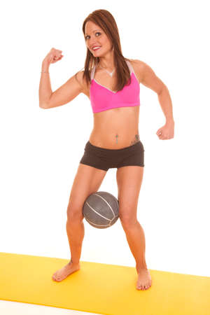 A woman is standing while holding a ball between her legs. photo