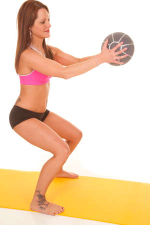 A woman is holding a ball and squatting. photo