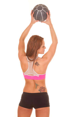 A woman holding a fitness ball is looking over her shoulder. photo