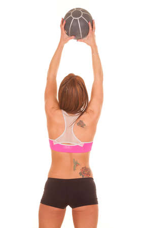 A woman is holding up a fitness ball above her head. photo