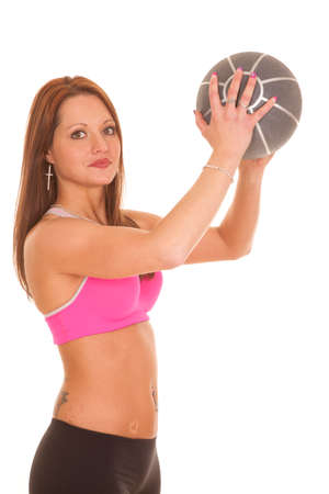A woman is holding up a fitness ball. photo