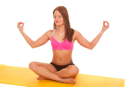 A woman is meditating on a yelllow yoga mat. photo
