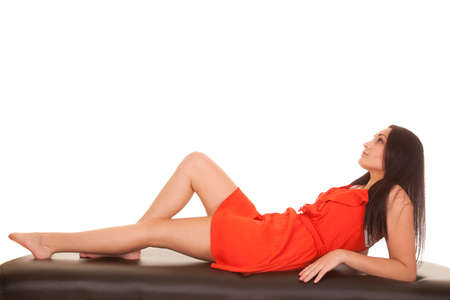 A woman in a red dress looking up laying back. photo