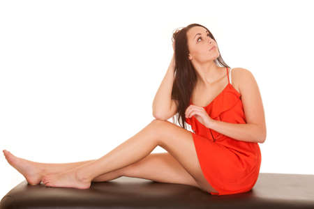 A woman in a red dress sitting looking up. photo