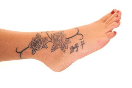 Een vrouw heeft een roos tatoeage op haar voet. Stockfoto
