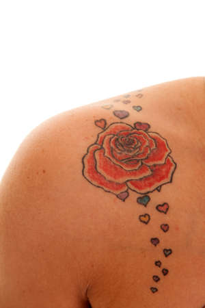 A woman has a rose tattoo on her shoulder. Stock Photo