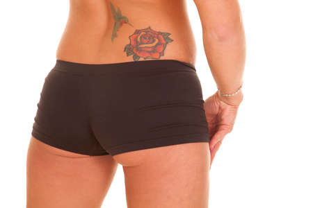A woman has a tattoo of a rose and a humming bird on her lower back. Фото со стока