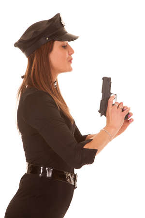 A policewoman is holding up a gun blowing on it. photo