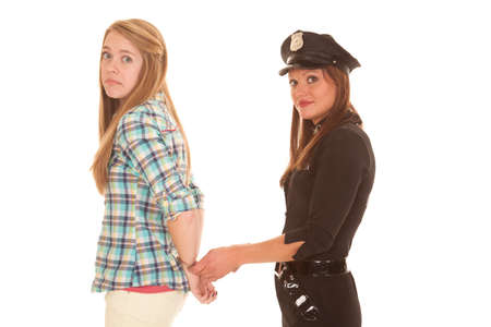 A woman is being handcuffed by a police woman. photo