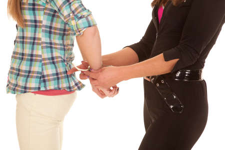A close up of two women and one is being handcuffed. Stock Photo