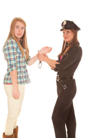 A woman is getting handcuffed by a cop. Stock Photo
