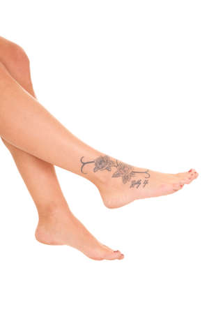 A woman is sitting and her foot has a tattoo on it. photo