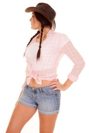 cowgirl hat: Una mujer de unos pantalones cortos de mezclilla cortos y la parte superior de la tela escocesa con un sombrero de vaquera. Ella es una chica de campo. Foto de archivo