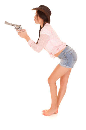 puckered lips: A woman in her pink plaid top and denim shorts holding out her pistol with her lips puckered