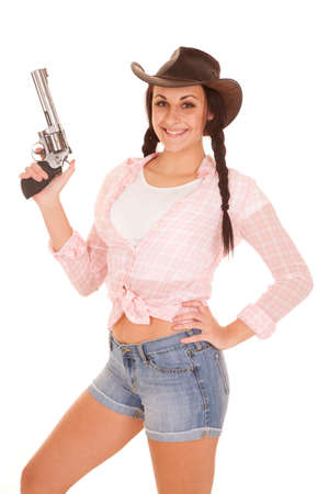 a woman with her gun pointing up with a smile on her face. photo