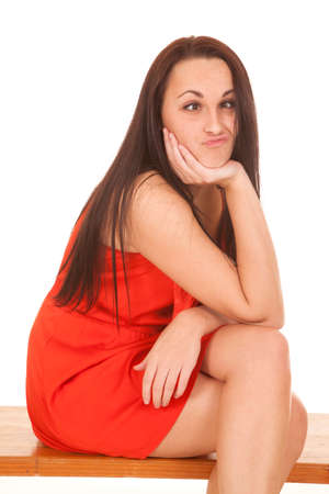 a woman sitting on a bench in her red dress with a funny expression on her face. photo