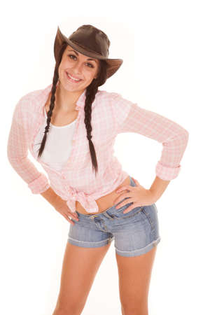 A woman with a big smile on her face with her hands on her hips in her plaid shirt and cowgirl hat.