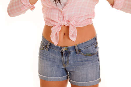 tomboy: A picture of a womans stomach in her pink plaid top and short jean shorts. Stock Photo