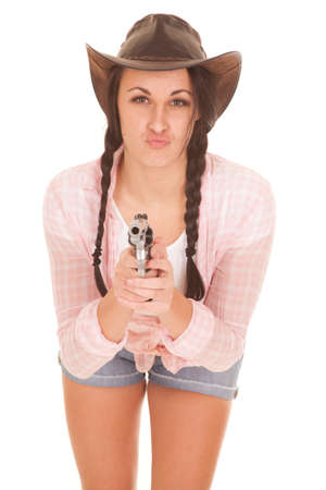 A woman in her cowgirl hat, plaid shirt holding on to a pistol. Imagens