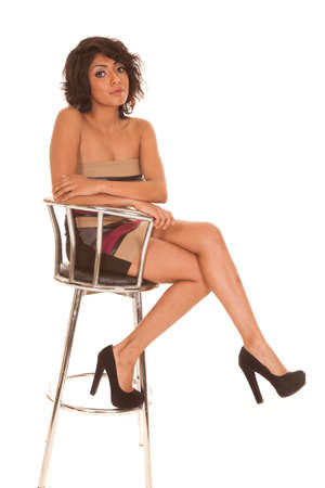 a Hispanic woman sitting on her stool in her short dress. photo