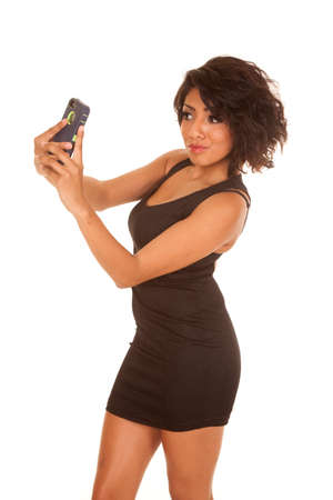 A hispanic woman in her little black dress, taking a picture of herself with her camera. photo