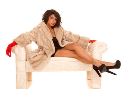 A Hispanic woman sitting on a bench in her fur coat with red gloves photo