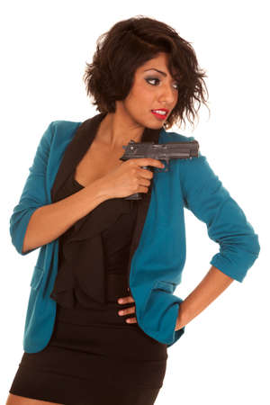 A Hispanic woman looking over her shoulder with her gun. Stock Photo - 23846179