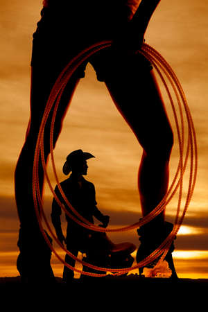A silhouette of a woman holding on to a rope with a cowboy inbetween her legs. photo