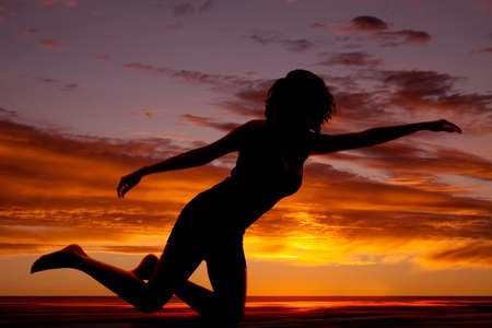 woman kneeling: A silhouette of a woman kneeling and reaching out. Stock Photo