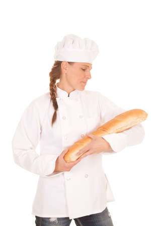 a woman baker holding a loaf of french bread in her arms.