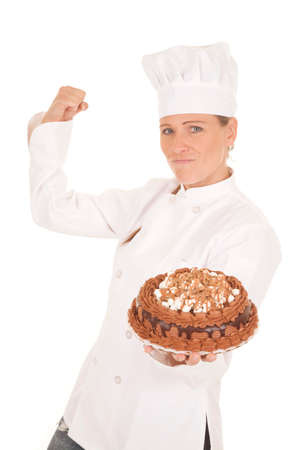 turned out: a woman baker holding on to her cake, flexing and showing off how good her cake turned out.