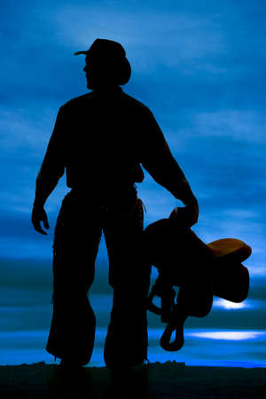 a silhouette of a cowboy holding on to his saddle. Stock Photo