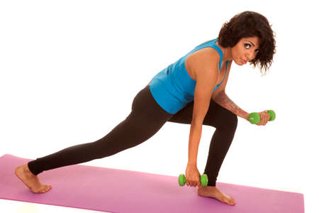An Hispanic woman working out with weights in a lung position.