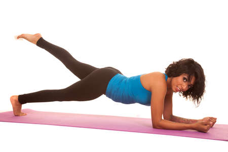 An hispanic woman working out doing plank with one leg up. photo