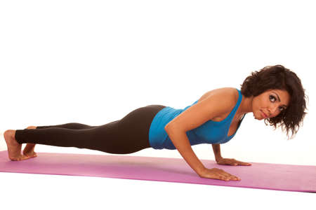 an hispanic woman doing a push up with a serious expression on her face. photo