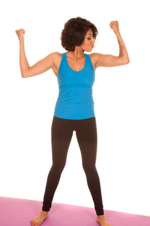 a hispanic woman looking at her arm muscles. photo